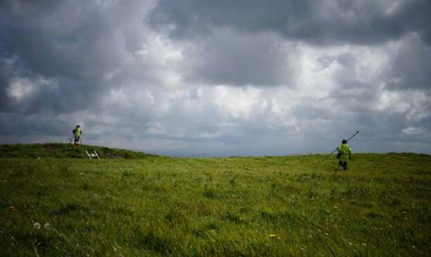 Dr. Catherine Frieman in a field in Cornwall with survey equipment. Image: ANU