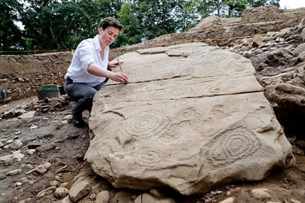Dr. Clíodhna Ní Lionáin, Devenish's lead archaeologist, cleaning the decorated kerbstone. (Devenish Nutrition)