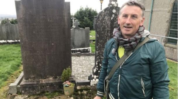 Dr Gerry Quinn at the grave of Reverend James McGirr (Credit: BBC)