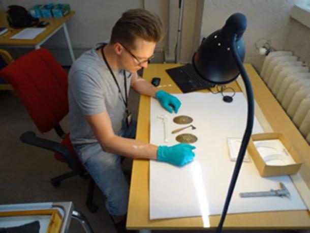 Dr. Leszek Gardeła studying a miniature axe and jewelry from a women`s grave in Svingesaeter, Norway. (Leszek Gardeła / Fair Use)