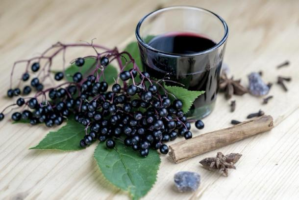 Elderberry remedy as a syrup with fresh elderberries in the background. (elfgradost / Adobe stock)