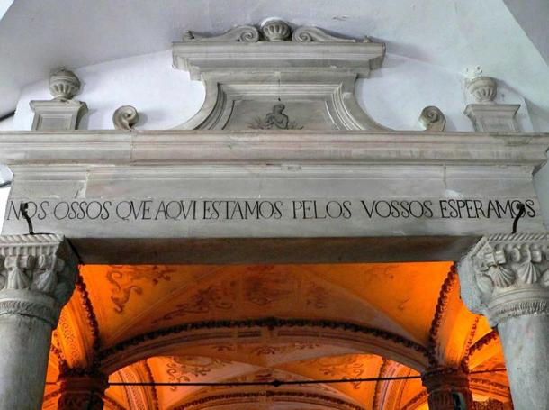 "Entrance to the chapel, with the message ""We bones, are here, waiting for yours."""
