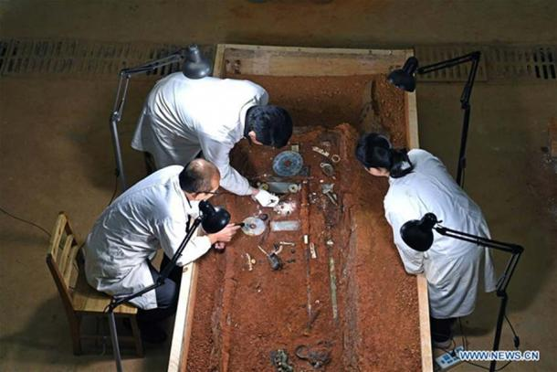 Examining some of the artifacts discovered in the disgraced emperor's son's tomb.