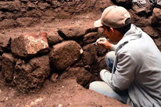 Examining the walls of the newly found Aztec era temple. (Melitón Tapia/INAH)