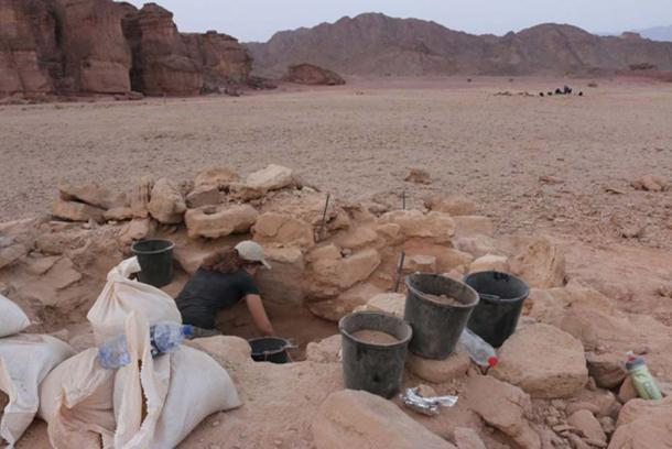 "Excavating the tumulus burial mound of the pregnant woman found at Timna. Hathor's temple and the sandstone formation known as ""Solomon's Pillars"" are on the left."