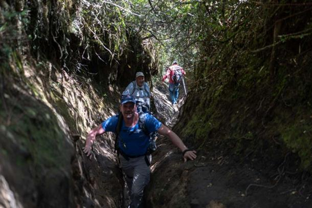 Expedition members clamber along an access trail to the mountain