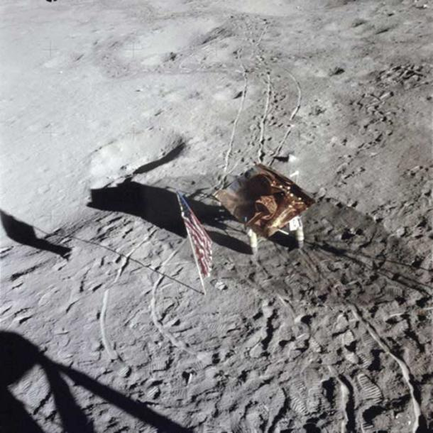 Footprints, wheel tracks and the Rickshaw–type portable workbench on the Moon, with the US flag in 1971. NASA