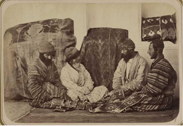Four Jewish men seated on the ground next to two large covered bundles, inspecting the dowry.