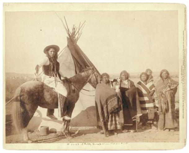 Four Lakota women hold three infants in cradleboards, with a Lakota man on horseback, in front of a tipi, on or near Pine Ridge Reservation in 1891. (Public Domain)