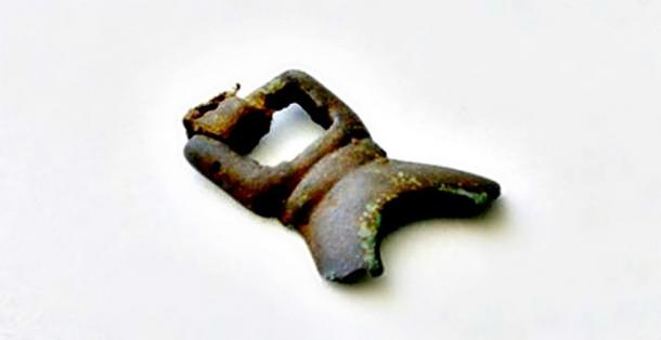 Fragment recovered from a brass buckle of the Thule culture that still retains some of its leather strap