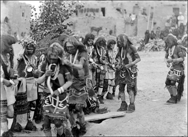 """Front row, Snake dancers near foot-drum, Oraibi village, Third Mesa, 1898, next row Antelope dancers, one with cottonwood wreath, medicine bowl, and water-sprinkler. Kisi (leaves of """"snake house"""") in the background."""