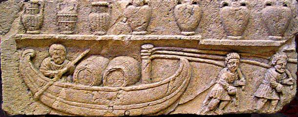 A Gallo-Roman relief depicting a river boat transporting wine barrels, an invention of the Gauls that came into widespread use during the 2nd century. Above, wine is stored in the traditional amphorae, some covered in wicker.