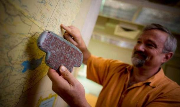 UC San Diego archaeologist Geoffrey Braswell holds a replica of the Maya jade pendant.