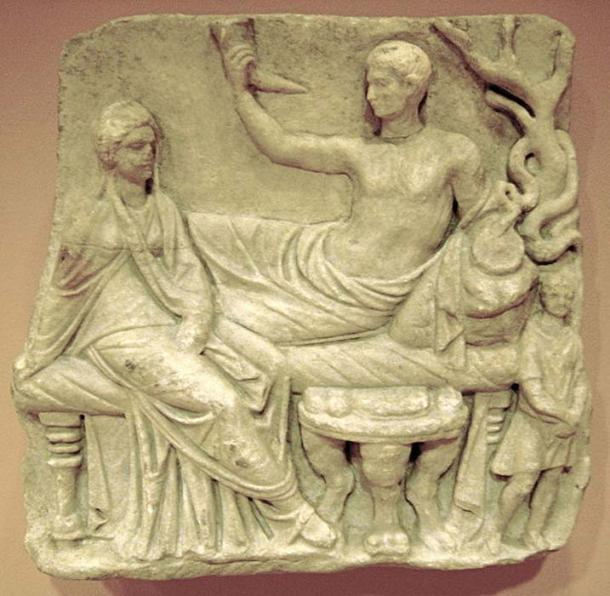 Grave relief showing the deceased and his widow in a funeral feast where they are depicted in a godlike manner. Roman marble work, 1st century AD. (Public Domain)