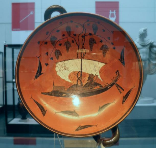 The Greek god of wine, Dionysus, crosses the sea in his dolphin boat with grape vines above the sail in a bowl from 530 B.C. by Exsekias.