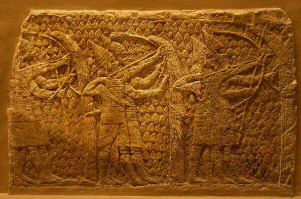 Heavy-armed archers in action. Assyrian, about 700-692 BC. From Nineveh, South-West Palace. These archers, the front one of whom is beardless, possibly an enuch, are each accompanied by a soldier whose duty it is to hold the tall shield in position and guard against any enemies who come too close.