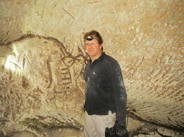 Hiker Ido Meroz near the engravings, including the symbol that has been identified as an ancient key.