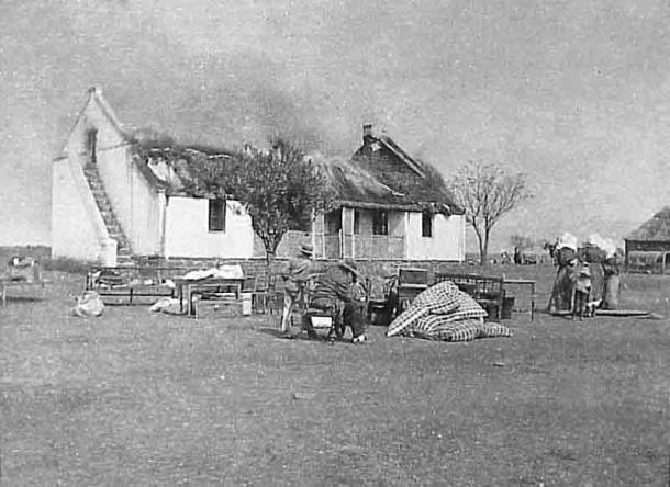 """One British response to the Boer's guerrilla war was a """"scorched earth"""" policy to deny the guerrillas supplies and refuge. In this image Boer civilians watch their house as it burns. (Public domain)"""
