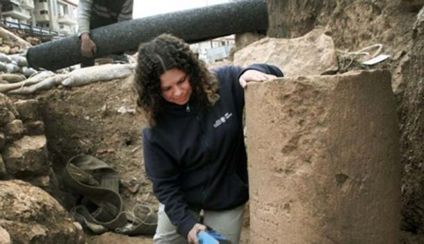 IAA archaeologist Danit Levy, with the stone bearing the most ancient inscription with the full name of Jerusalem, as it is spelled in modern times. Image: Yuli Schwartz/IAA