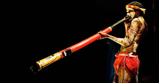 An Indigenous Australian playing the Didgeridoo