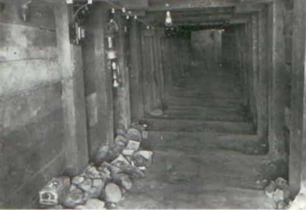Interior of the main tunnel at Spearhead Mound. Note electric lighting and boxes of excavated material along the left wall. (James L. Murphy)