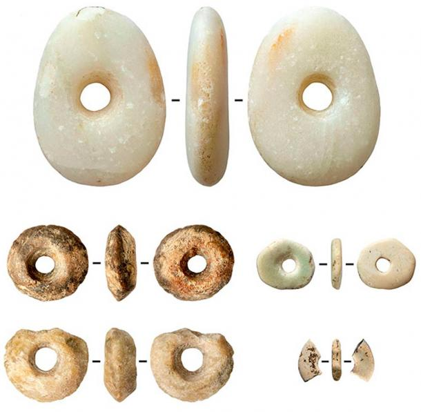 Ivory and talc (soapstone) beads and a marble pebble with traces of ocher.
