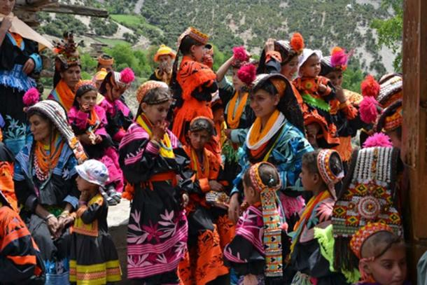 Kalash women and children in traditional bright costume.