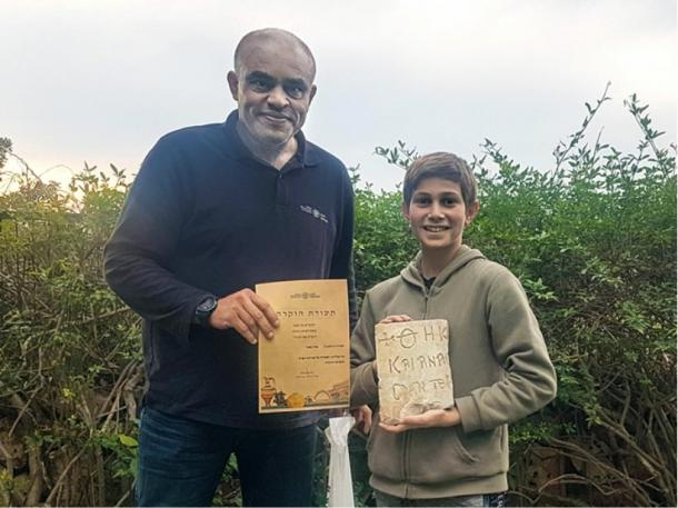 Karem Said, Haifa district archaeologist at the IAA, awards Stav Meir with a certificate of appreciation for his find of the 1,500-year-old Byzantine inscription near Caesarea. (Karem Said/ Israel Antiquities Authority)