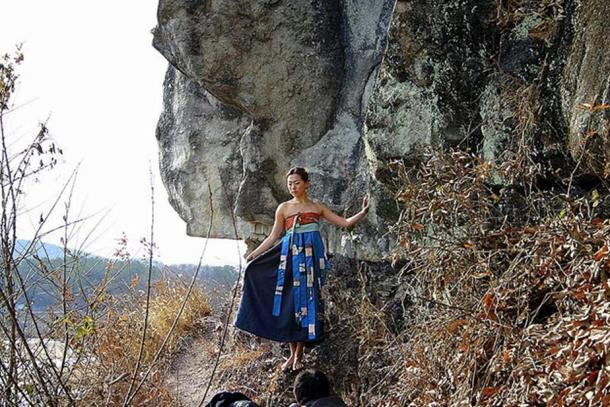 Korean woman posing by a cliff near Andong City where the poem was found.