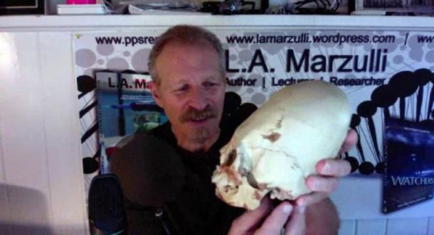 LA Marzulli holding up a replica of one of the Paracas skulls that was tested