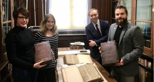 Left to right: Leah Tether, Laura Chuhan Campbell, Michael Richardson, and Benjamin Pohl with the books in Bristol Central Library's Rare Books Room. The team of experts investigating further if the pieces hold any secret about the legends of Arthur, Merlin, and the Holy Grail. (University of Bristol)