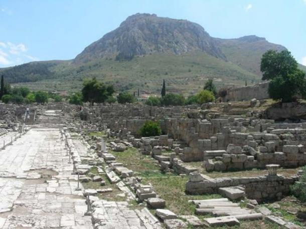 Lechaion Road, entering from the north-west (top) and facing south-east, with Acrocorinth in the background (bottom).