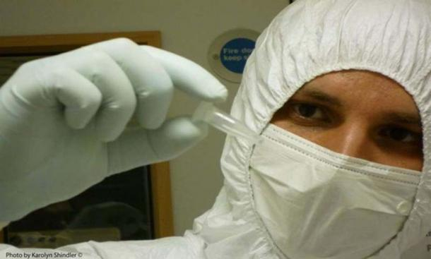 Linus Girdland-Flink working in the ancient DNA laboratory. To avoid introducing contaminant DNA, ancient DNA researchers dress up in full-body coveralls and face masks.