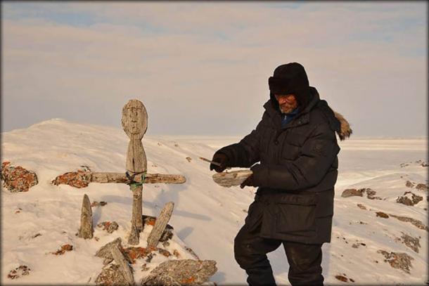 Local Nenets Andrey Vylko repairs the idol. Image: Yamal RGO