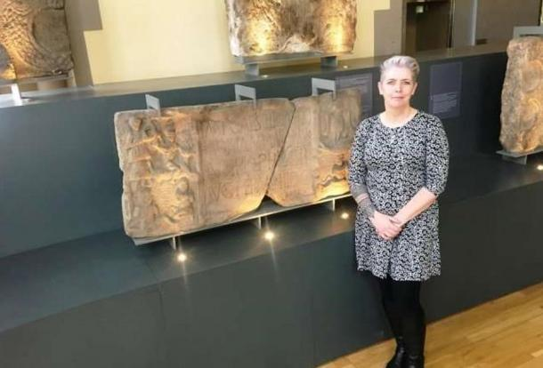 Dr. Louisa Campbell with the Summerston distance stone at The Hunterian Museum.