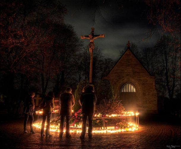 Lutheran Christians in Sweden praying and lighting candles in front of the central crucifix of a graveyard. (Public Domain)