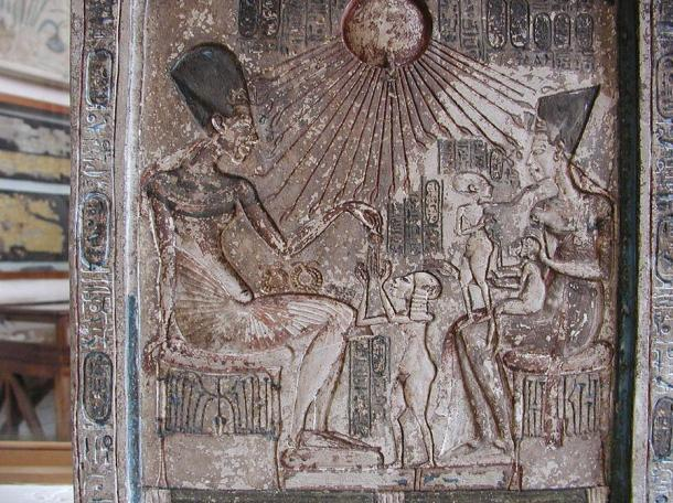 Stele: Akhenaten sits on a stool on the left side, handing a jewel to his eldest daughter (and possibly Tut's wet nurse) Meritaten, who stands in front of him. On the right plays with two of their daughters on her lap, Meketaten and Ankhesenpaaten.