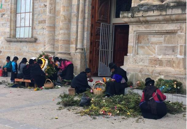 Men and women of Saraguro in traditional clothing prepare floral arrangements outside the town cathedral.