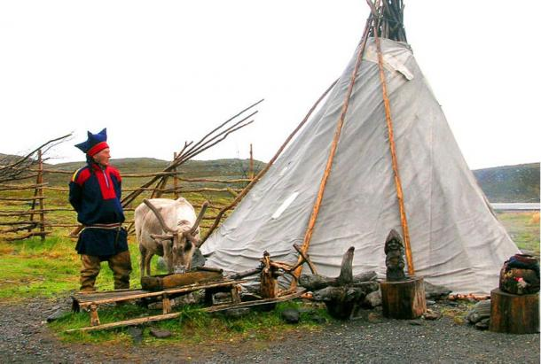 Modern Sámi man beside lavvu nomadic house, Norway