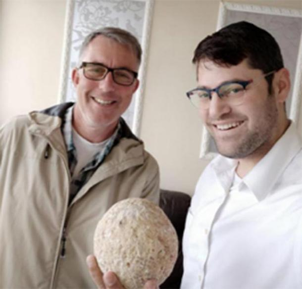 Moshe Manies (right) and Uzi Rotstein (left) of the Israel Antiquities Authority with the stolen ballista stone. (Moshe Manies / IAA)