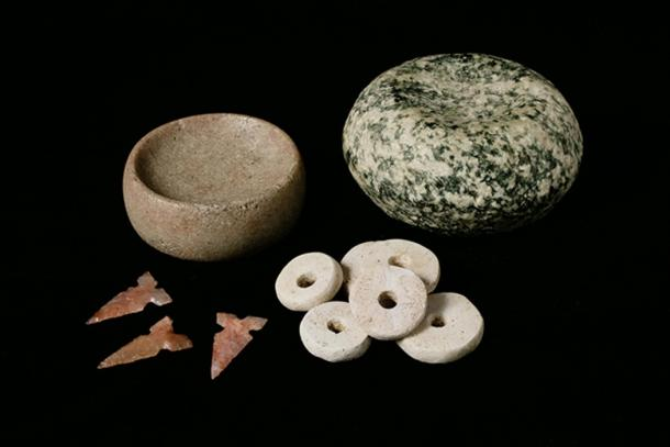 Mound 72 at Cahokia held several mass graves but also burials of high-status individuals, some of which included items like these artifacts. Pictured here are chunky stones likely used in games, Cahokia-style tri-notched projectile points, and marine shell disc beads like those used in the beaded burial at Cahokia.