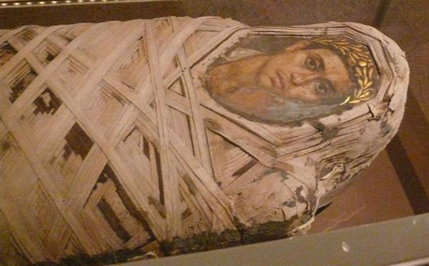 Mummy with an inserted panel Fayum portrait of a male youth. Roman period. Encaustic on limewood, linen, human remains.