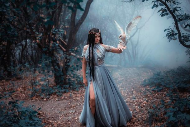 Mysterious sorceress in a cold forest in the fog with a white owl.