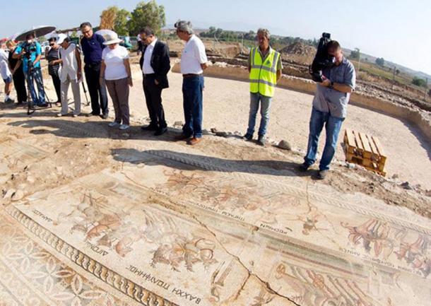 Officials examining part of the mosaic found in Akaki village.