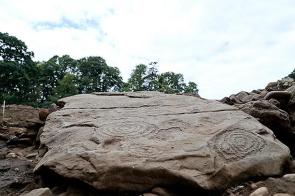 One of the 6 kerbstones is covered with petroglyphs. (Devenish Nutrition)