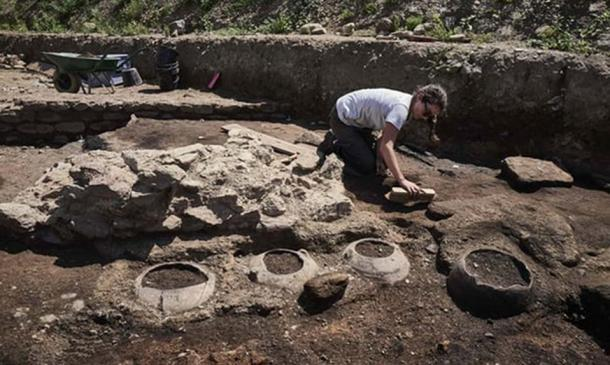 One of the French archaeological team cleaning household artifacts at the site at Sainte-Colombe in Vienne, France (Credit: Jean-Philippe Ksiazek/AFP)