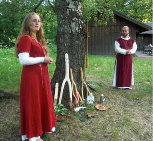In Sweden, a Pagan priestess and a priest perform a ceremony during an annual meeting. Under the tree are images of Norse gods Thor, Frigg, Freyr, Freya and Forseit with a ceremonial hammer, a drinking horn and an oath ring. Hanging on the birch tree, which is sacred to the goddess Frigg, hangs a birch trumpet.