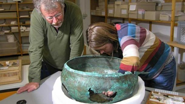 Paleobotanist Manfred Rösch and conservator Tanja Kreß sample the ancient cauldron in Tübingen, Germany.