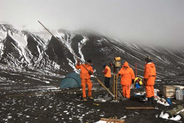 Perforations on permafrost in Crater Lake. David is at the side of the drill with a hood. Deception Island, January 2009.