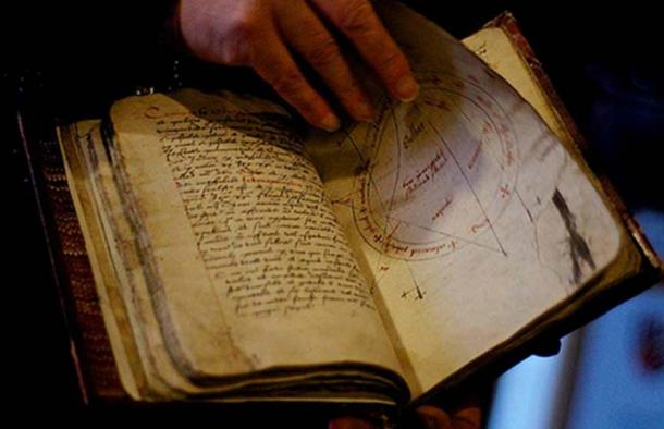 Person thumbing through a grimoire.